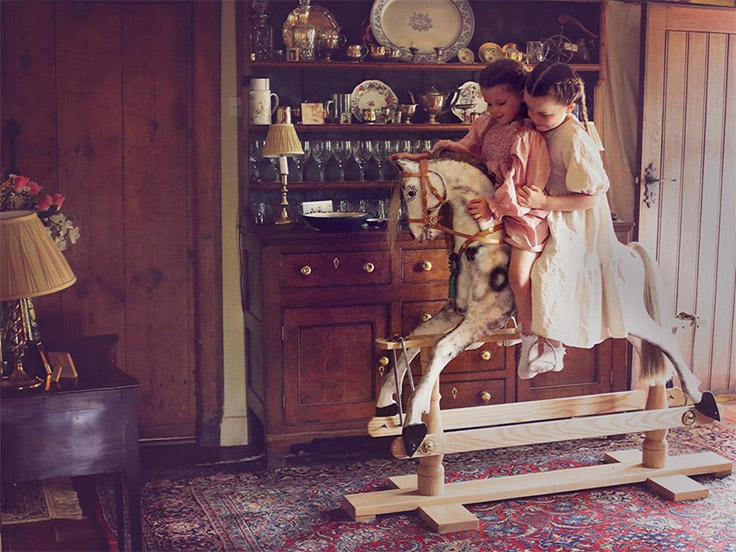 Two young girls riding a rocking horse together in a sitting room