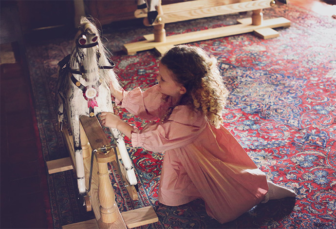 A small girl playing with a rocking horse at home