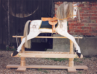 A large dapple grey rocking horse stood outside