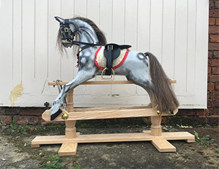 A small antique style dapple grey rocking horse stood outside