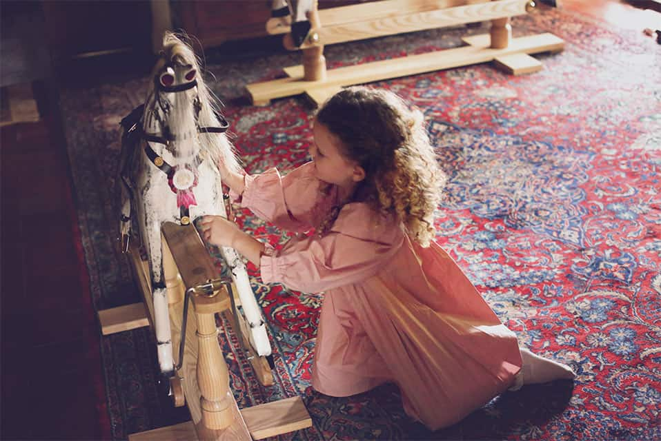 A young girl playing with a rocking horse at home
