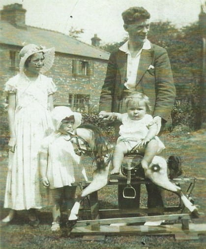A toddler sitting on a rocking horses surrounded by family