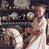 A young girl riding a rocking horse in a large sitting room