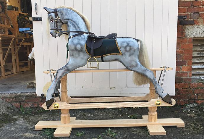 An antique style dapple grey rocking horse stood outside
