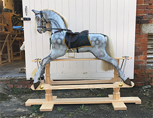 An antique style dapple grey rocking horse stood outside