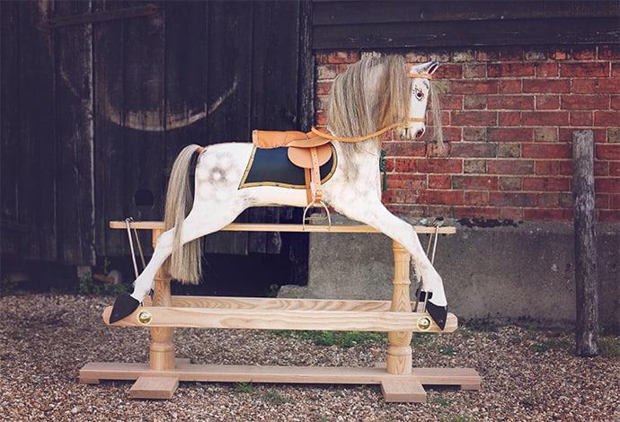 A large dapple grey rocking horse stood outside