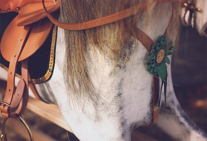 The front torso of a dapple grey rocking horse wearing green badge