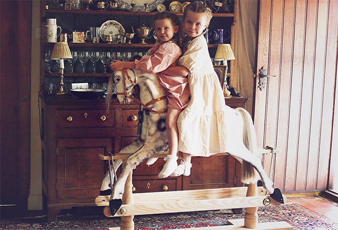 A pair of young girls riding a rocking horse in a sitting room