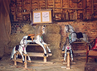 Two dapple grey rocking horses in a stable
