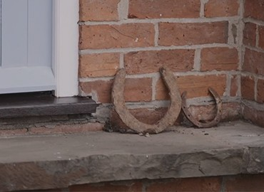 Two horseshoes on a wall at a farm